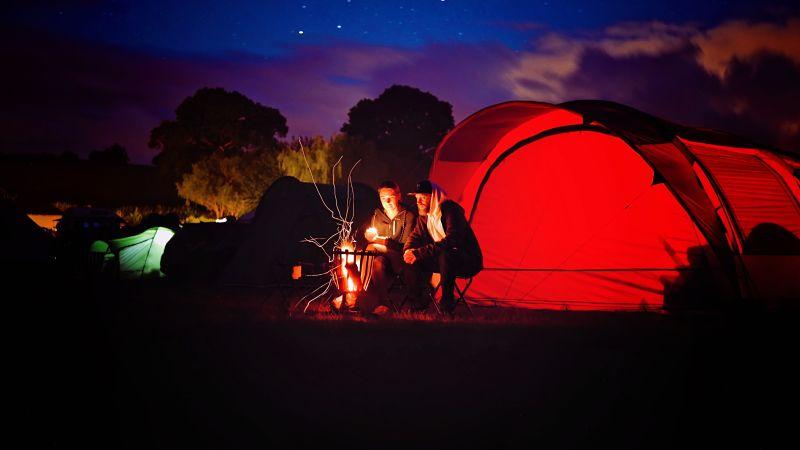 Imagen de un campamento de noche en la que hay dos personas sentadas frente al fuego. Al fondo hay varias tiendas de campaña, de las que destaca una de grandes dimensiones de color rojo. Esta imagen se usa para acompañar una entrada en la que se explica qué es TECO.